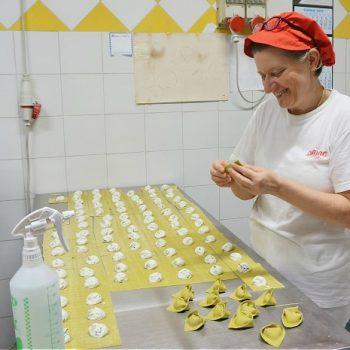 イタリアの手作りパスタ店でラビオリ包み