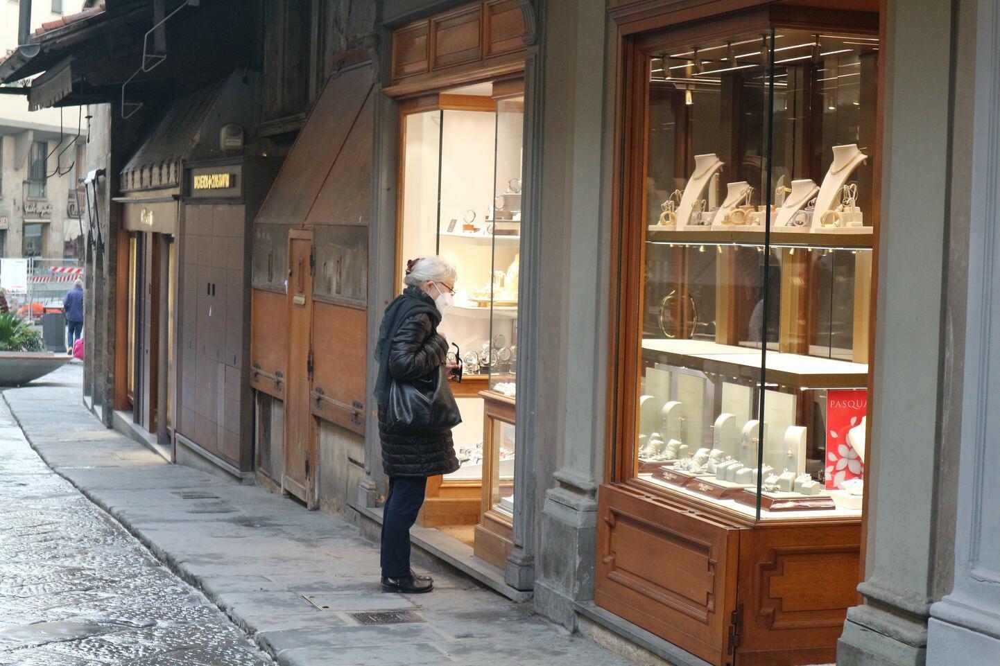閉店しているジュエリー店の商品を眺める女性